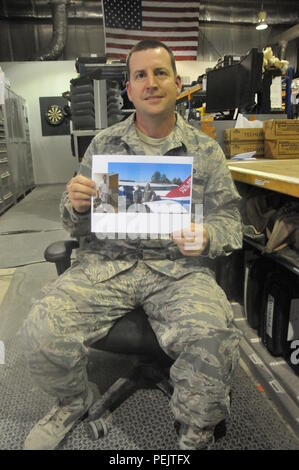 Staff Sgt. Daniel Stein, 8th Expeditionary Air Mobility Squadron crew chief, holds a picture of his son, Gregory. In November, Gregory was in an all-terrain vehicle accident and fractured his C-1 vertebrae. The 8th EAMS, Qatari Emiri Air Force and the Boeing Company put together a care package for Gregory. The care package consisted of mementos from 8th EAMS members, a QAEF C-17 replica and a Qatar flag. . (U.S. Air Force photo courtesy of Staff Sgt. Stein/Released) - Stock Photo