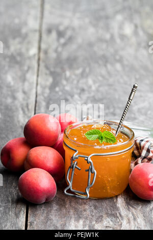 Red apricot  jam with caramel in a clear glass jar on wooden table - Stock Photo