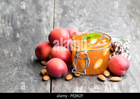Red apricot  jam with almonds in a clear glass jar on wooden table - Stock Photo