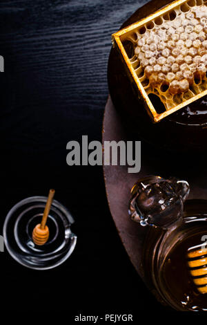 fresh honey in white bucket and in glass jar, with honeycomb, wooden sticks - Stock Photo
