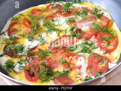 Scrambled eggs with tomatoes and dill in a frying pan close up - Stock Photo