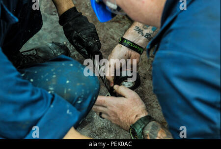 150612-N-MG976-032  NEWPORT NEWS, Va. (Dec 2, 2015) -- Sailors assigned to the Nimitz-class aircraft carrier USS Abraham Lincoln (CVN 72) work together to prepare a cable for use in a catapult on the flight deck, Dec. 2. Lincoln is undergoing a Refueling and Complex Overhaul (RCOH) at Newport News Shipbuilding, a division of Huntington Ingalls Industries. (U.S. Navy photo by Mass Communication Specialist 3rd Class Rob Ferrone/Released) - Stock Photo