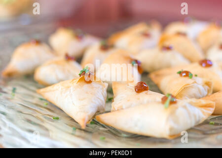 Filo pastry parcels on a glass plate. - Stock Photo
