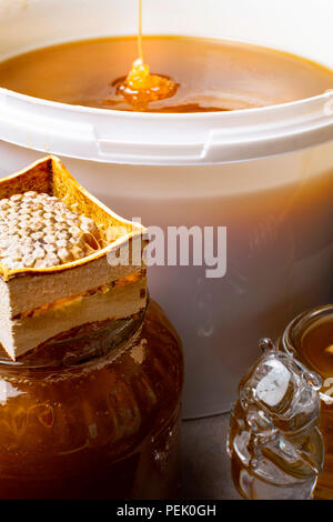 fresh honey in white bucket and in glass jar, with honeycomb - Stock Photo