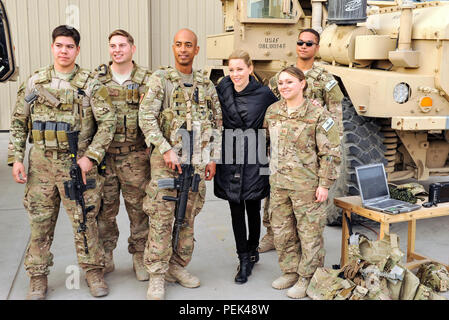 Task Force Crimson Airmen poses for a photo with actress Elizabeth Banks at Bagram Air Field, Afghanistan, Dec. 8, 2015. Celebrities came to Bagram to visit with the troops, sign autographs and put on a concert in an aircraft hangar. (U.S. Air Force photo by Capt. Bryan Bouchard/Released) - Stock Photo