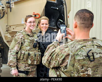A Task Force Crimson Airman poses for a photo with actress Elizabeth Banks at Bagram Air Field, Afghanistan, Dec. 8, 2015. Celebrities came to Bagram to visit with the troops, sign autographs and put on a concert in an aircraft hangar. (U.S. Air Force photo by Capt. Bryan Bouchard/Released) - Stock Photo