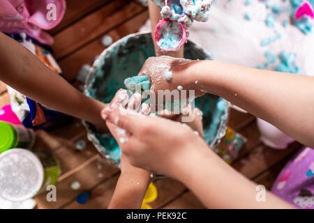 A group of young girls, children make a mess with frothy slime at a birthday party - Stock Photo