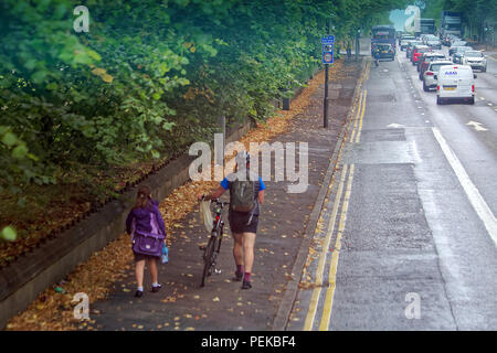 father and daughter walking to school on first day of term on pavement sidewalk pushing bike next to road traffic - Stock Photo