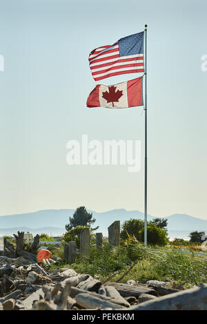 US and Canadian Flag. US and Canadian Flags fly in Point Roberts, Washington State. Mt Baker in the background. - Stock Photo