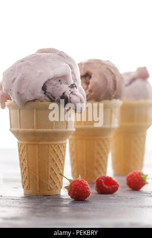 Three ice cream cones and a few raspberries.