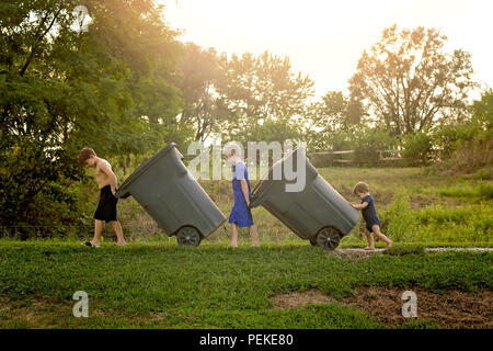 Three young boys taking out the trash bins - Stock Photo