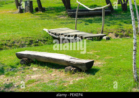 An old wooden bench rudely made from a log of wood against a background of green grass. - Stock Photo