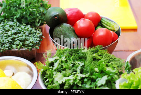 Fresh vegetables tomatoes, avocados, greens on the table, cooking process - Stock Photo