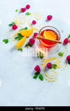 Honey tea from above. Decorative honey swirls, lemon slices, berries and tea in a glass cup on a white wooden background with copy space. Creative food flat lay - Stock Photo