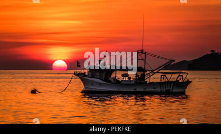 Landscape view of a sunset over the south China sea in Kota Kinabalu (Borneo, Malaysia), with an old fishing boat in the foreground - Stock Photo