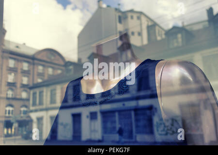 Reflection in the window of the city with a dress on a mannequin - Stock Photo