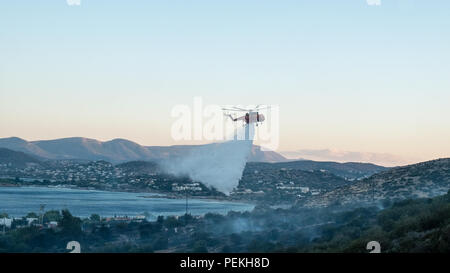 Fire emergency services spraying water preventing the fire from spreading further on the mountains. Saronida, East Attica, Greece, Europe. - Stock Photo