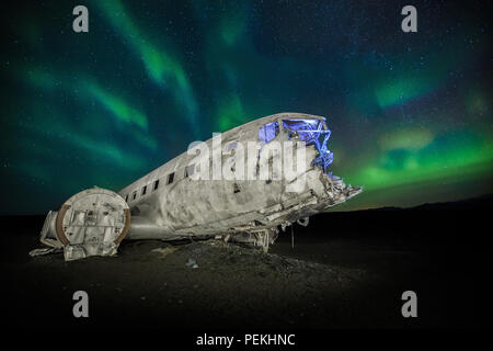 The crashed DC-3 Plane wreck with Northern Lights & Aurora Borealis at Solheimasandur, Iceland - Stock Photo