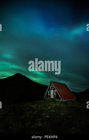 Emergency Mountain Hut / Shelter with the Northern Lights & Aurora Borealis, Snaefellsnes Peninsula, Iceland - Stock Photo