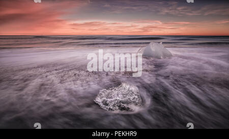 Glacial Ice washed ashore on the beach at Jokulsarlon Black Sand Beach also known as Breidamerkursandur, Iceland - Stock Photo