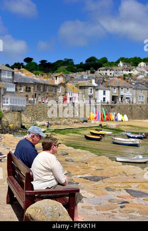 2 two People sitting on benches in the summer sunshine in the fishing village of Mousehole,Cornwall,England,UK - Stock Photo