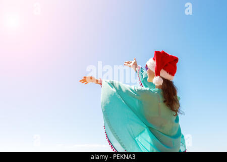 Woman with hands outstretched to the sky on the beach. Rear view of a tourist in a santa hat and bikini enjoying the Christmas holidays on a sunny day - Stock Photo