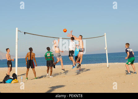 Young men playing volleyball on the spanish beach - Stock Photo