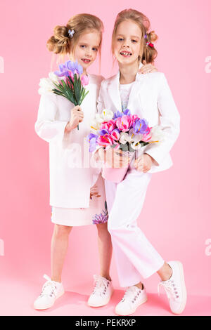 Twins girls in light clothes with bouquets of flowers stand on a pink background. - Stock Photo