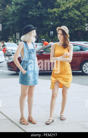Portrait of two white Caucasian unformal young girls hipster students teenagers friends in dresses, hats, outside standing talking in urban city stree - Stock Photo