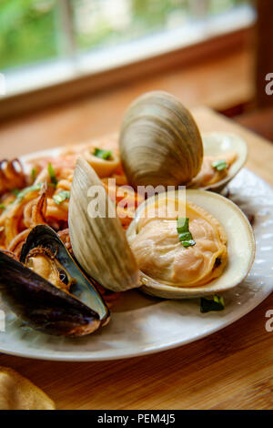 Italian seafood pasta pescatore with clams mussels and squid - Stock Photo