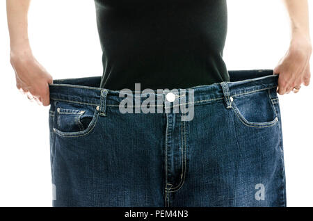 Woman showing how much weight she lost by wearing her old jeans. Weightloss concept. - Stock Photo
