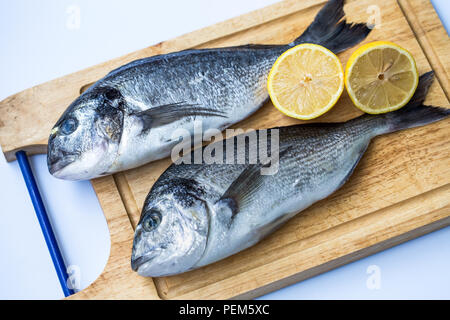 Couple of fresh raw sea bream fish (Sparus aurata) or Orata on wooden chopping board on a white background - Stock Photo