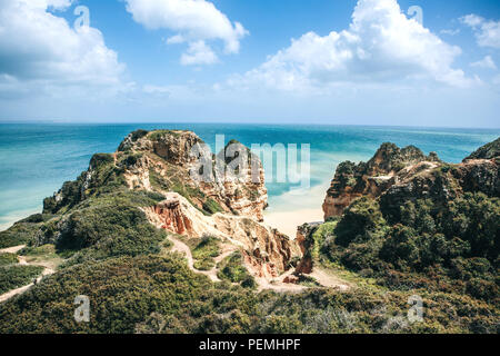 Beautiful views of the Atlantic Ocean and the rocks off the coast of Portugal next to the city called Lagos. From above the blue sky and clouds on a sunny day. Amazing natural landscape. - Stock Photo