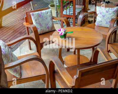 Wooden armchairs with pillows, round wooden table with flower in pot on table and wooden bookshelf on wooden plank floor in cafe. - Stock Photo