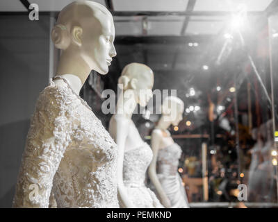 White female mannequin in wedding dress in showcase. Bridal dresses on the mannequins in wedding window display with light on wedding suit shop backgr - Stock Photo