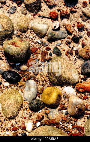 Beautiful colorful stones, sea shells and geological rocks containing minerals of sea lying underwater on the sea floor in the shallow waters. - Stock Photo