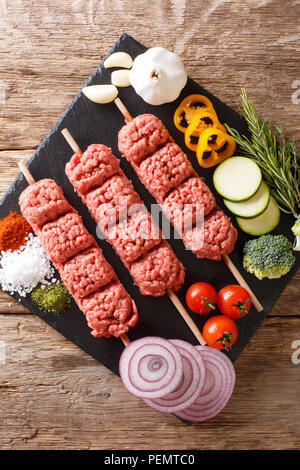 Homemade kebabs from raw minced meat on skewers with spices, herbs and vegetables close-up on the table.  Vertical top view from above - Stock Photo