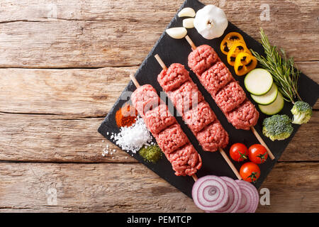 Homemade kebabs from raw minced meat on skewers with spices, herbs and vegetables close-up on the table.  Horizontal top view from above - Stock Photo
