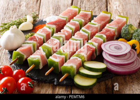 For barbecue raw shish kebab with pepper and lard on skewers close-up and ingredients, vegetables, spices, herbs on the table. horizontal - Stock Photo