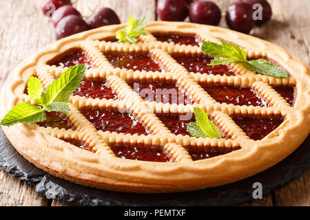 Italian crostata shortbread cake with cherries and mint closeup on a table. horizontal - Stock Photo