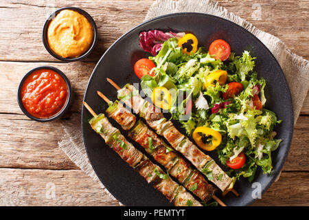 Delicious kebab on skewers with fresh vegetable salad on a plate and sauce close-up on the table. Horizontal top view from above - Stock Photo