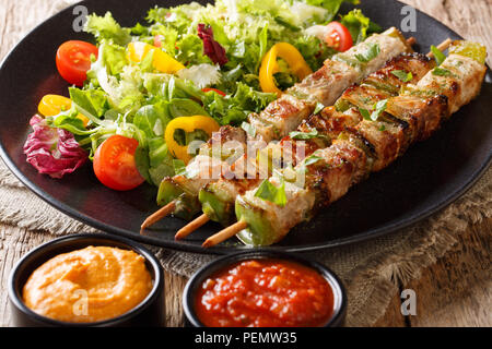Grill kebab with vegetables on skewers with fresh salad on a plate and sauces close-up on a table. horizontal - Stock Photo