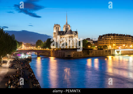 Notre Dame de Paris with cruise ship on Seine river at night in Paris, France - Stock Photo