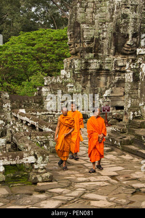 Siem Riep, Cambodia / Oct 9, 2011: Three monks walking among ancient temple ruins - Stock Photo