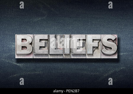beliefs word made from metallic letterpress on dark jeans background - Stock Photo