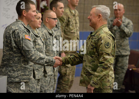 U.S. Army Gen. Frank Grass, chief of the National Guard Bureau, right, shakes hands with Capt. Waylon Tomac as he visits with members of the North Dakota Army and Air National Guard who have distinguished themselves within their organizations as Grass conducts a town hall style of briefing at the Raymond J. Bohn Armory, Bismarck, N.D., Dec. 12, 2015. (U.S. Air National Guard photo by Senior Master Sgt. David H Lipp/Released) - Stock Photo