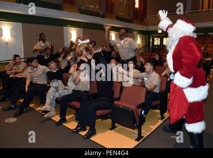 LAKE VILLA, Ill. (Dec. 14, 2015) – Santa tosses Candy Canes to Junior Reserve Officers Training Corps (NJROTC) cadets  during holiday concert performed by Navy Band Great Lakes at the Hyman G. Rickover Naval Academy here, Dec. 13. (Official U. S. Navy photo by Scott A. Thornbloom/Released) - Stock Photo