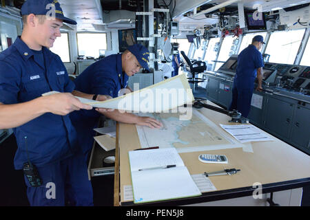 Petty Officer 3rd Class Stanley Adamson and Petty Officer 1st Class Silvestre Suga, both boatswain's mates aboard USCGC Walnut, track the ship's position via paper charts during transit offshore Kauai, Dec. 4, 2015. Walnut and a six-member dive team from Regional Dive Locker Pacific worked together to conduct salvage and recovery operations of aids to navigation buoys located near shoal water. (U.S. Coast Guard photo by Petty Officer 3rd Class Melissa E. McKenzie/Released) - Stock Photo