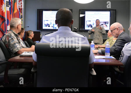 Col. Joseph Martin (standing), director of the Center for Excellence in Disaster Management and Humanitarian Assistance (CFE-DM), provides a CFE-DM orientation brief to Gen. Darren W. McDew, commander, and other distinguished guests from U.S. Transportation Command Dec. 16. The discussion explored collaborations in disaster response training and education. - Stock Photo