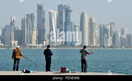 Fishermen fishing against the backdrop of West Bay, Doha, Qatar - Stock Photo